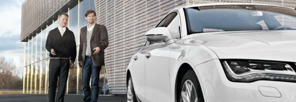 A salesman leading a customer to a car featured in a blog post about CPO Audi cars
