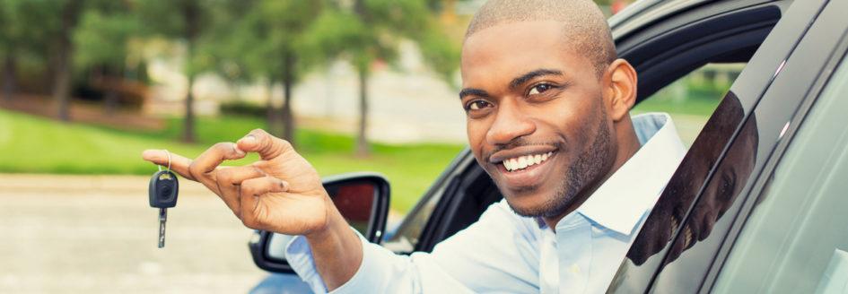 Smiling man dangling car keys from driver side window